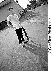 Skateboarder - A young skater teen posing in an urban area...