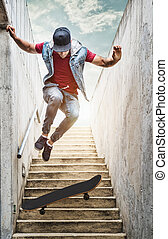 Skateboarder boy jumps off the stairs