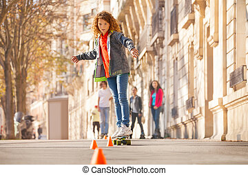 Skateboarder curving around the cones at side walk