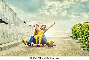 Skateboarder girlfriends roll down the slope