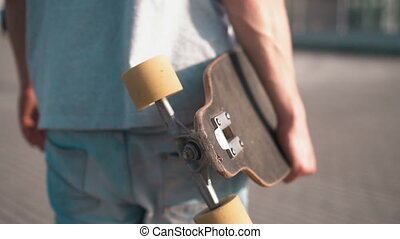 Skateboarder Holds Skateboard - Young skateboarder in gray...