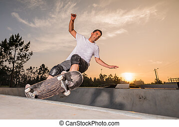 Skateboarder in a concrete pool at skatepark on a beatiful ...