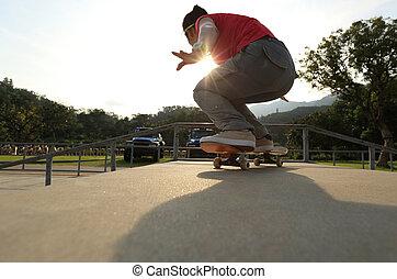 skateboarder legs doing a trick ollie at skatepark