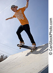 Skateboarder on a Ramp - A young man skateboarding down a ...