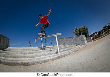 Skateboarder on a slide at the local skatepark.