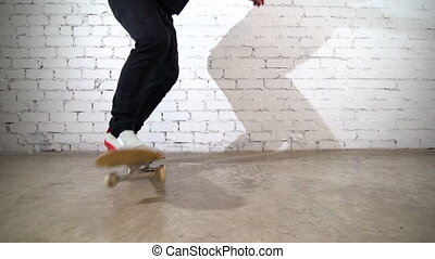 Skateboarder performing skateboard trick in the studio. Athlete practicing stunt jump on yellow background, preparing for competition. Extreme sport, youth culture
