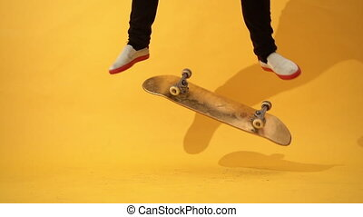 Skateboarder performing skateboard trick - kick flip in the studio. Athlete practicing stunt jump on yellow background, preparing for competition. Extreme sport, youth culture