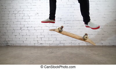 Skateboarder performing skateboard trick - kick flip on concrete. Athlete practicing jump on white background, preparing for competition. Extreme sport, youth culture