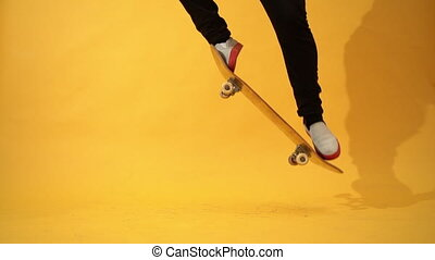 Skateboarder performing skateboard trick - ollie in the studio. Stunt shot of athlete practicing jump on yellow background, preparing for competition. Extreme sport, youth culture