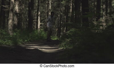 skateboarder ride in forest