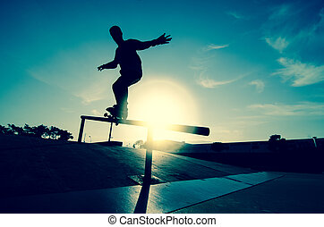 Skateboarder silhouette on a grind at the local skatepark.