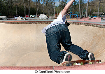 Skateboarder Skating the Bowl - Action shot of a young...