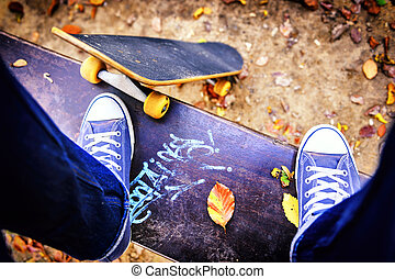 Skateboarder standing on a bench in city park