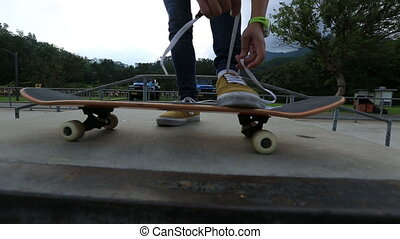 skateboarder tying shoelace at skatepark