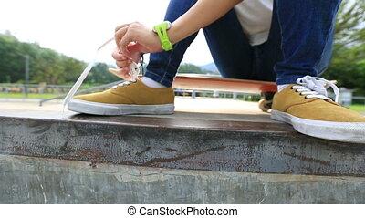 skateboarder tying shoelace
