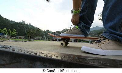 skateboarder tying shoelace - skateboarder tying shoelace at...
