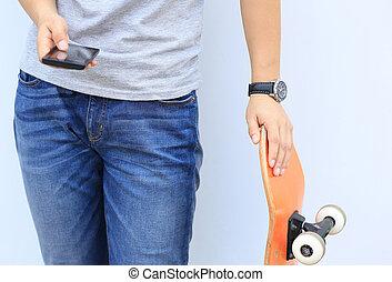 skateboarder use cellphone lean on wall