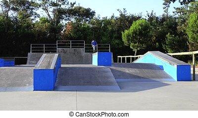Skateboarder doing an ollie on ramp on a local skate park.