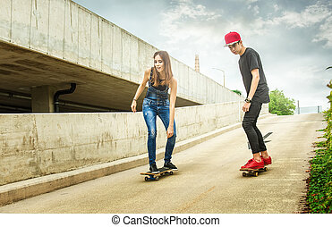 Skateboarder woman and man rolling down the slope