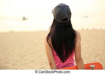skateboarder woman on beach