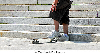 Skateboarder - Young man with standing on his skateboard