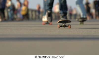 Skateboarders ride on the road in the park.