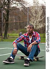 Skateboarding Guy Taking a Rest