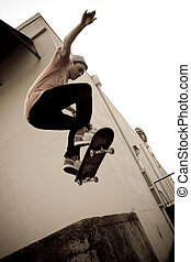 Skateboarding Jump - A young skateboarder launches off a...