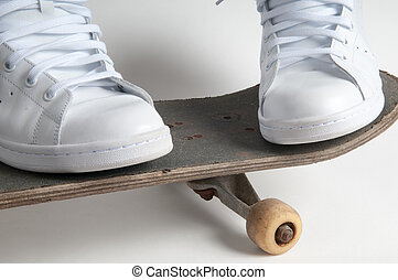 skateboarding person stands with feet apart on an old skateboard