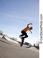 Skateboarding Tricks - A young skateboarder doing a stunt in...