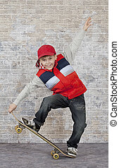 Skater boy crouching on his skateboard in front of brick ...