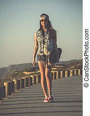Skater Girl - Beautiful skate girl walking while holding a...
