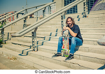 Skater is resting on the stairs, next to the rails