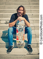 Skater is resting with skate board on the stairs