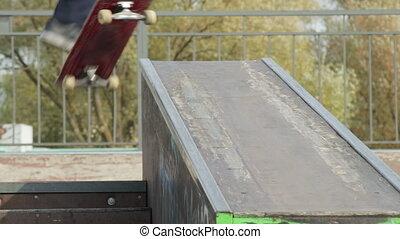 Skater make 50-50 grind down the ledge in skatepark,...