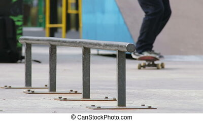Skater make grind feeble 180 on rail in skatepark, close-up...