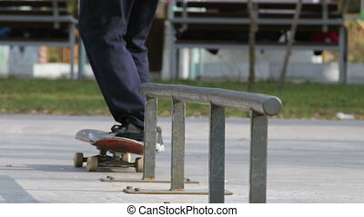 Skater make grind trick feeble on rail in skatepark,...