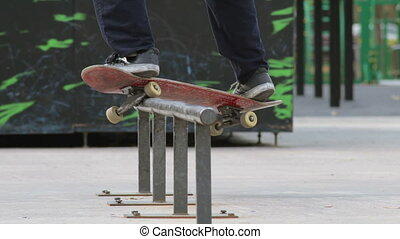 Skater make grind trick smith on rail in skatepark, close-up...