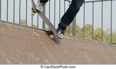 Skater make trick feeble stand on edge of ramp radius,...