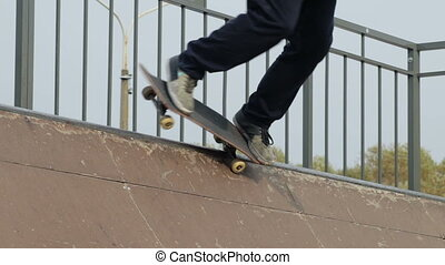 Skater make tricks on the edge of wooden mini ramp, close-up view in slowmotion