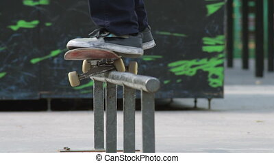 Skater rides on a rail with trick 50-50 grind, close-up view...