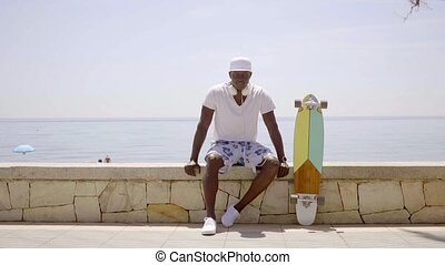 Skater seated on stone wall by ocean on sunny day while...