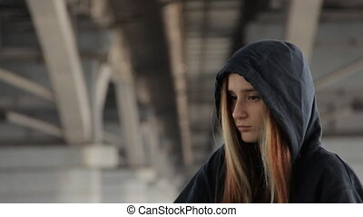 Skater style teenage girl in a hoody with the hood on and...