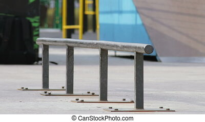 Skater takes a skateboard and tries the trick on the rail in...