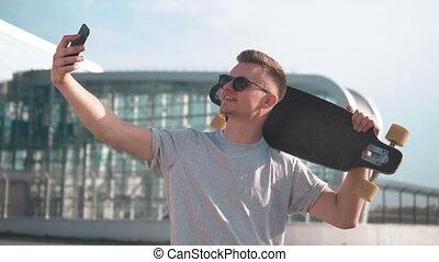 Skater Takes Selfie - Smiling skater taking selfie with...