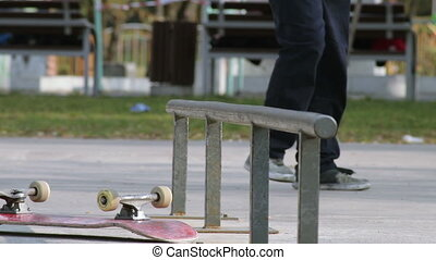 Skater trying trick on rail and fails, bring up skateboard...
