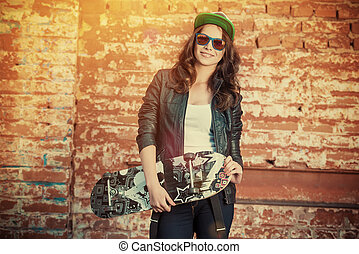 skater young - Modern girl teenager stands with skateboard...