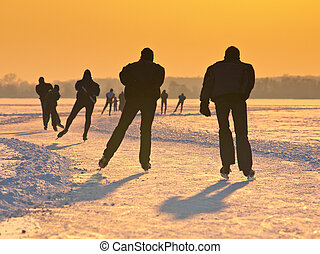 Skaters during sunset - Skaters on a dutch lake seen on...