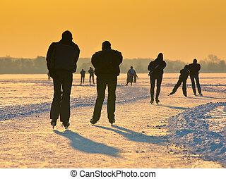 Skaters under setting sun - Skaters on a dutch lake seen on...