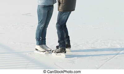 Skating rink romance - Young people holding each other on...